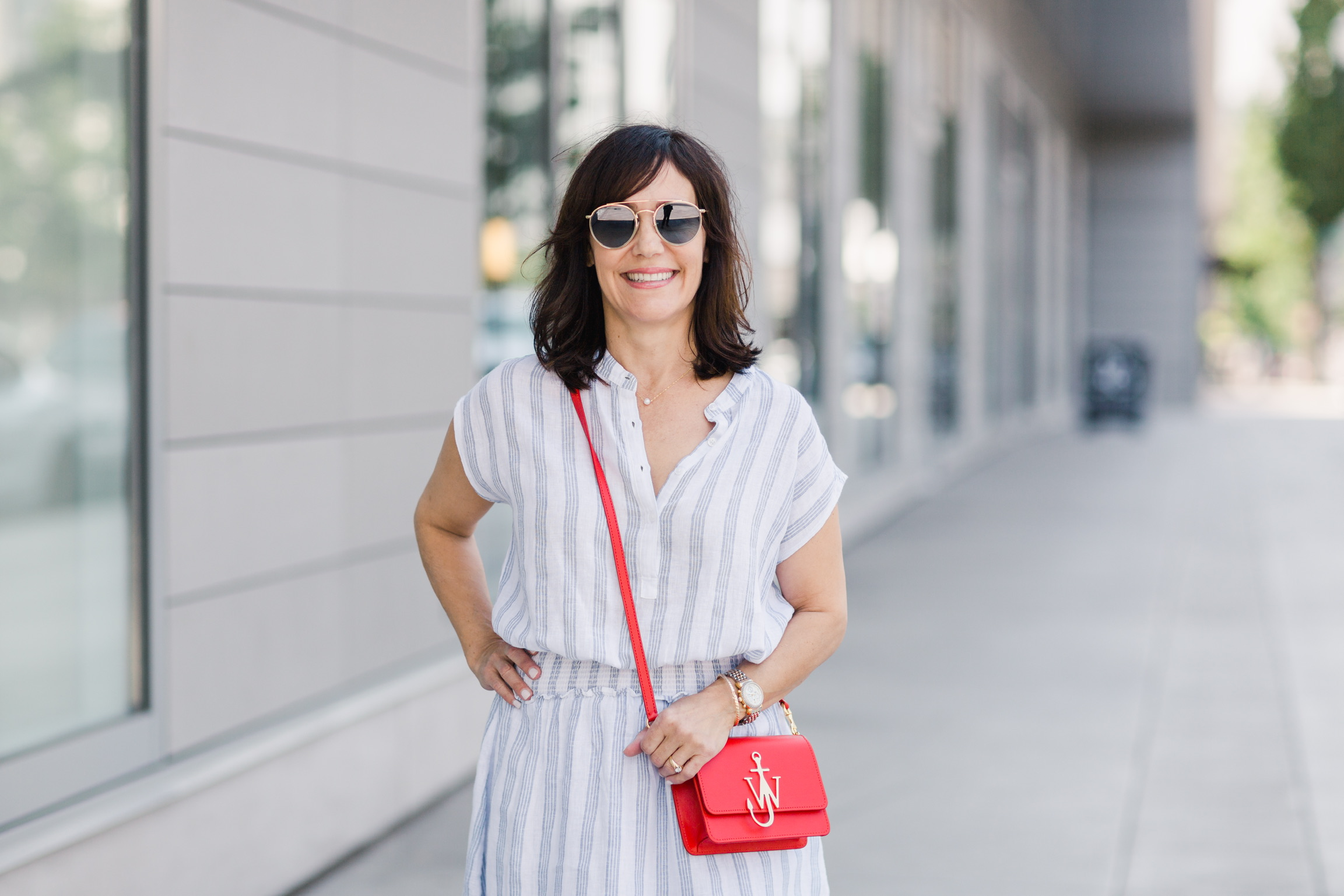 Fashion blogger wearing a white and blue striped Rails sundress and red crossbody bag